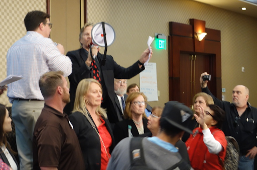 Matt Pakucko, president of Save Porter Ranch, uses a bullhorn to disrupt and take over a meeting of state regulators in February 2017