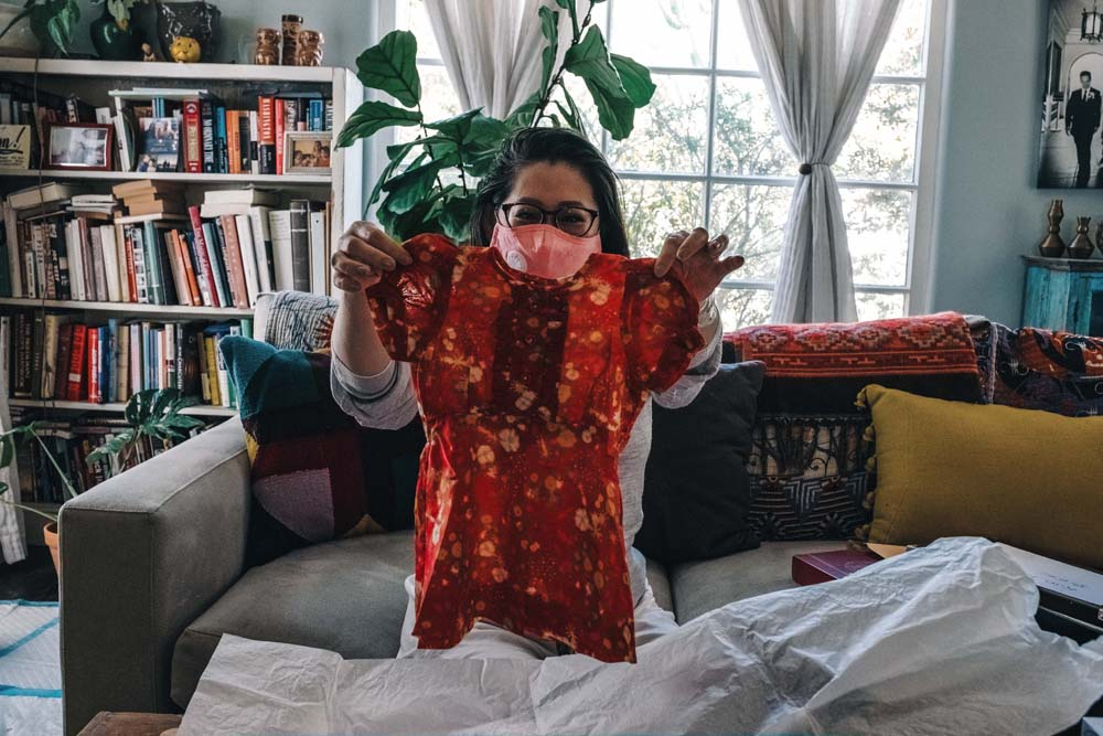 Luu-Ng holds the dress she was wearing, as a toddler, when her family escaped Vietnam by boat.
