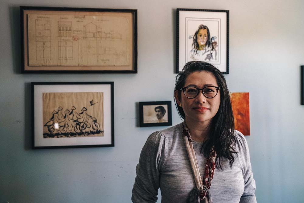 Human rights lawyer Kim Luu-Ng in front of a wall in her Alhambra home displaying art and blueprints from her childhood home to honor her family's roots in Vietnam.